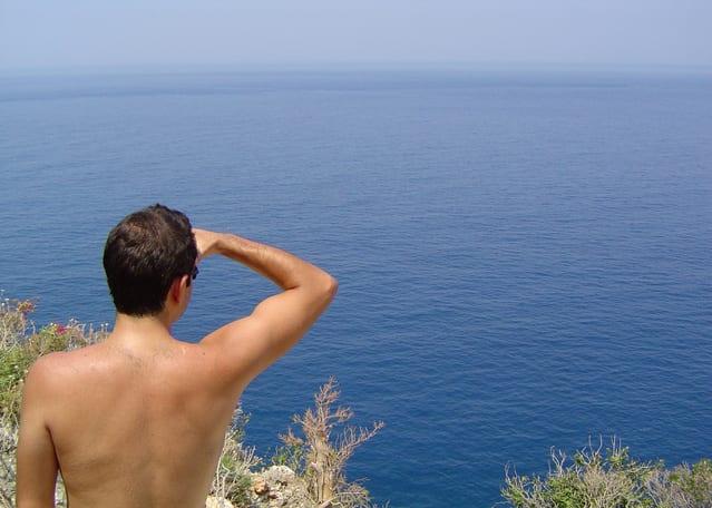 man shirtless looking at ocean