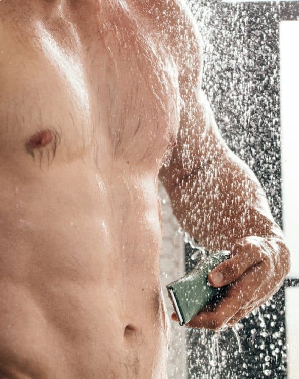 man using meridian trimmer in shower